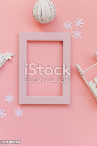 istock Simply minimal composition winter objects pink frame ornament fir tree sled isolated on pink pastel trendy background 1190462954