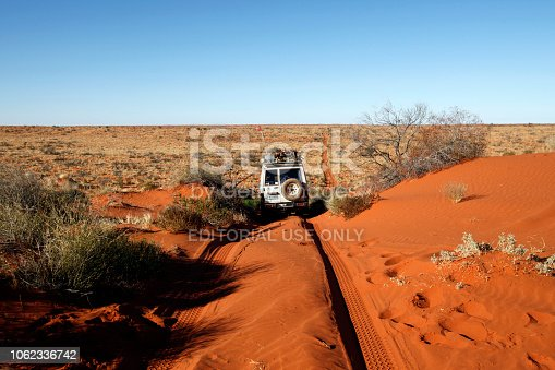 Simpson Desert, Australia - June 21, 2009: A four wheel drive vehicle drives on a track in the Simpson Desert. The Simpson Desert  is a large area of dry, red sandy plain and dunes in the Northern Territory, South Australia and Queensland  in central Australia. It is the fourth largest Australian desert,  with an area of 176,500 km² and is the world's largest sand dune desert.