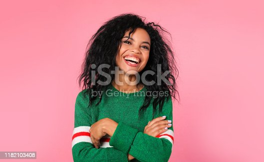 857924506 istock photo Sincere expression. Beautiful African ethnic woman in a green sweatshirt with white and red stripes is posing with folded arms, laughing while looking at the camera. 1182103408