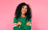istock Sincere expression. Beautiful African ethnic woman in a green sweatshirt with white and red stripes is posing with folded arms, laughing while looking at the camera. 1182103408