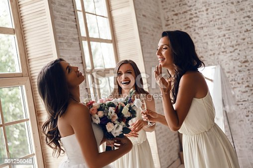 Attractive young woman holding a wedding bouquet and smiling while her girlfriends drinking champagne