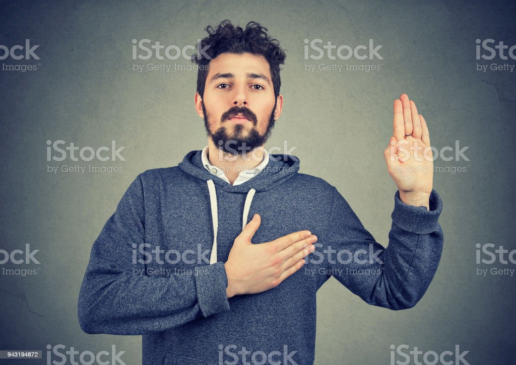 sincere man swearing with hand on heart stock photo