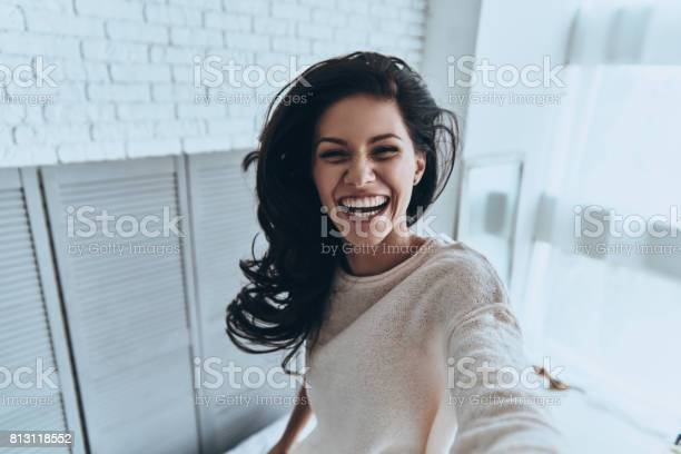 Self portrait of attractive young woman looking at camera and smiling while standing in the bedroom at home