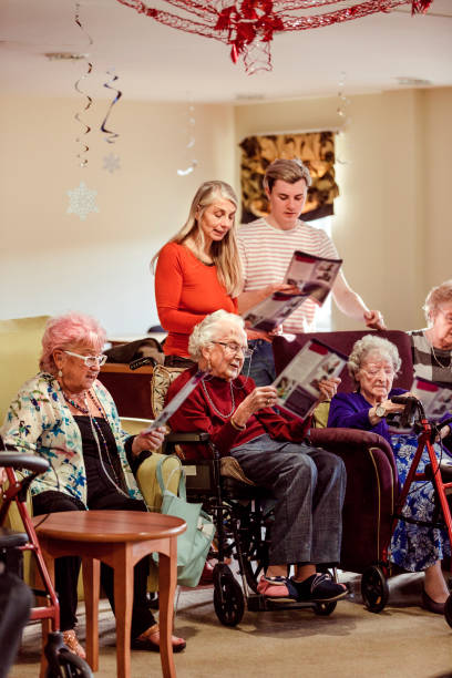 sing-a-long in the care home - full length of senior people singing together against white stock photos and pictures