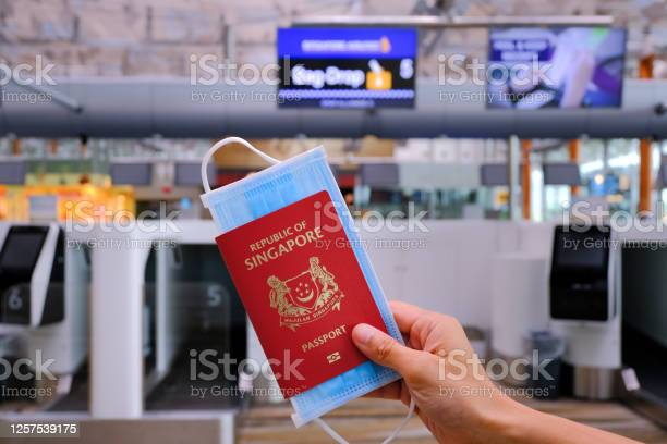 Singapore airport hand holding singapore passport and face mask at picture id1257539175?b=1&k=6&m=1257539175&s=612x612&h=fch9nvcllvghbxlmhmr1cfwnckolbd8omnqxltxj2ze=