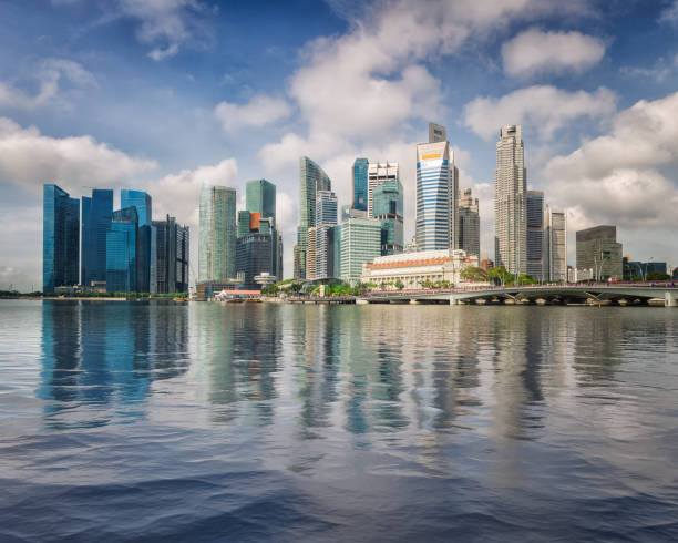 singapore business center skyline and blusky in day time with reflection on water - singapore nature stock photos and pictures