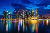 Central Business District in Singapore at Dusk. Beautiful Reflexions on the water of Marina Bay. Singapore City, Central Business District, Asia. XXXL Photo, made with Canon 5DSR at 50 MPixel Resolution.