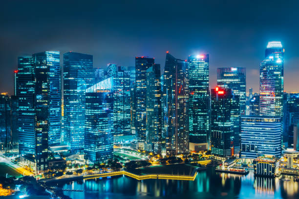 singapore city skyline. business district aerial view. downtown landscape reflected in water at night in marina bay. travel cityscape - singapore stock photos and pictures