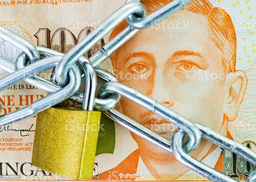 Singapore currency with a chain and lock stock photo