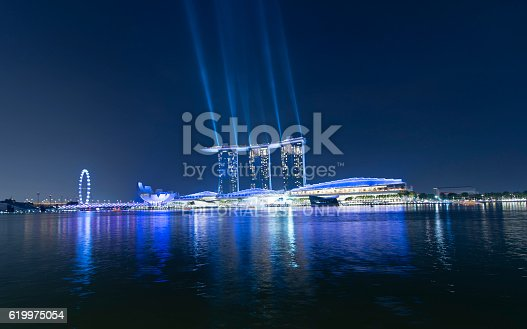Singapore, Singapore - September 5, 2016: Night view of the Marina Bay Sands Hotel in the centre. The ArtScience Museum in Singapore is showing to the left. On top of the buildings a laser light show is running.