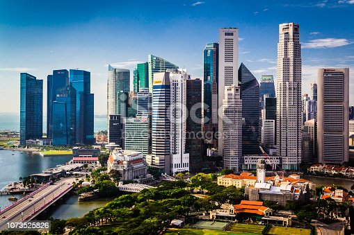 The skyscrapers of downtown Singapore stand tall on a clear blue sky day in the Lion City. Vibrant cityscape background with copy space.