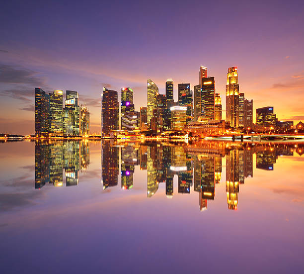 Singapore Financial District Singapore financial district at sunset dramatic sky. merlion fictional character stock pictures, royalty-free photos & images
