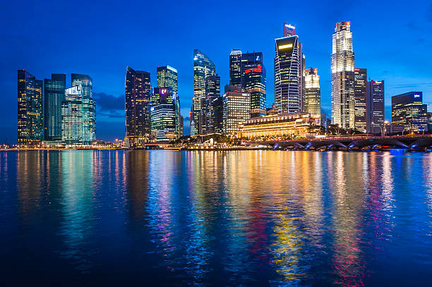 Singapore illuminated neon skyscrapers of Downtown Core overlooking Marina Bay The neon lights and colourful glow of the futuristic skyscrapers, waterfront restaurants and luxury hotels of Singapore's Downtown Core reflecting in the still waters of Marina Bay. merlion statue stock pictures, royalty-free photos & images