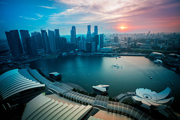 singapore marina bay and business district skyline at sunset - marina bay sands stock photos and pictures