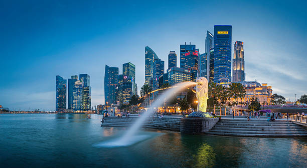 "Singapore Merlion Fountain CBD skyscrapers overlooking Marina Bay at dusk ""Singapore, Singapore - 14th February 2012: The crowded cityscape of Central Business District skyscrapers overlooking the Merlion fountain on the Marina Bay waterfront at dusk as tourists and locals enjoy the warm evening promenade, Singapore. Composite panoramic image created from six contemporaneous sequential photographs."" merlion statue stock pictures, royalty-free photos & images"