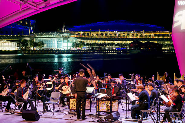 Singapore, Open Air Orchestra at the Esplanade Theater Singapore, Singapore - August 05, 2012: The Young Musician Orchestra plays a public free summer night concert at the bay side of the Esplanade Theater.  esplanade theater stock pictures, royalty-free photos & images