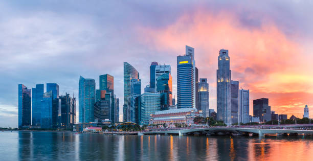 Singapore Skyline at Marina Bay at Twilight with glowing sunset illuminating the clouds stock photo