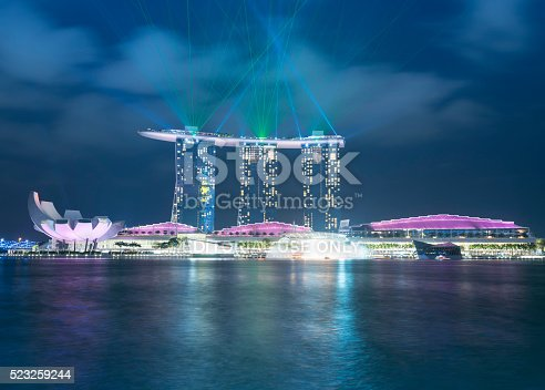 Singapore, Singapore - April 10, 2016: Night view of the Marina Bay Sands Hotel in the centre. The ArtScience Museum in Singapore is showing to the left. On top of the Marina Bay sands Hotel a laser light show is running.