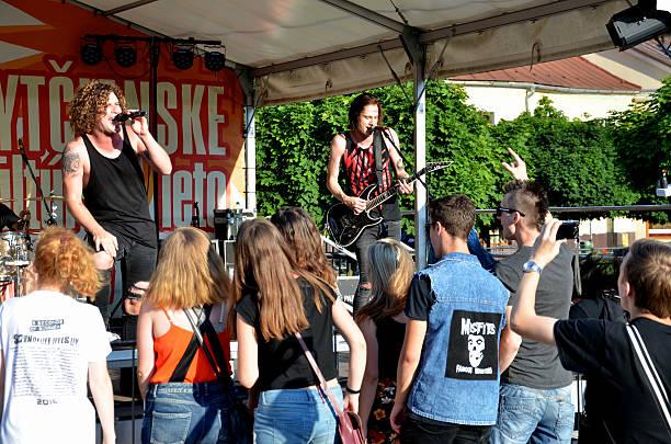 La cantante y guitarrista en frente de grupo de gente joven. - foto de stock