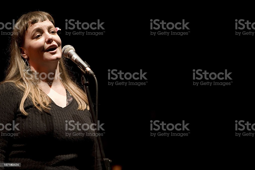 Singer in the spot light at the microphone stock photo