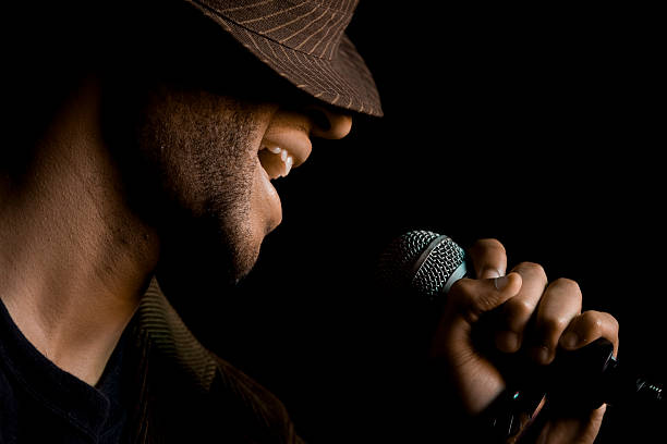 Singer on Stage A man is singing into the mic on stage. singer stock pictures, royalty-free photos & images