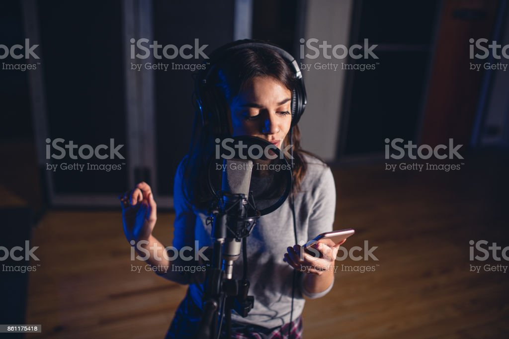 Singer recording song for her album in studio stock photo