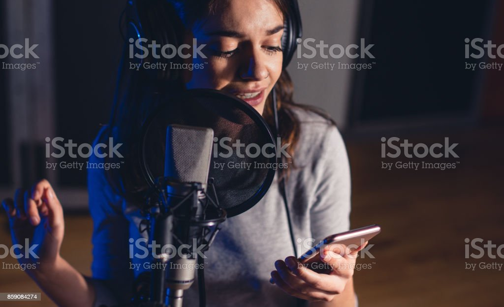 Singer singing in the recording studio with mobile phone stock photo