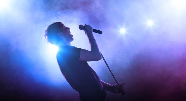 Singer with a microphone performing on stage Young vocalist with a microphone singing on stage singer stock pictures, royalty-free photos & images