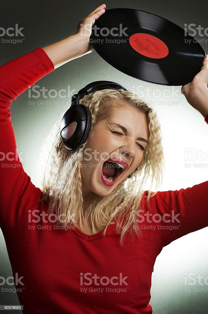 Singing beautiful woman with headphones and vinyl record royalty-free stock photo