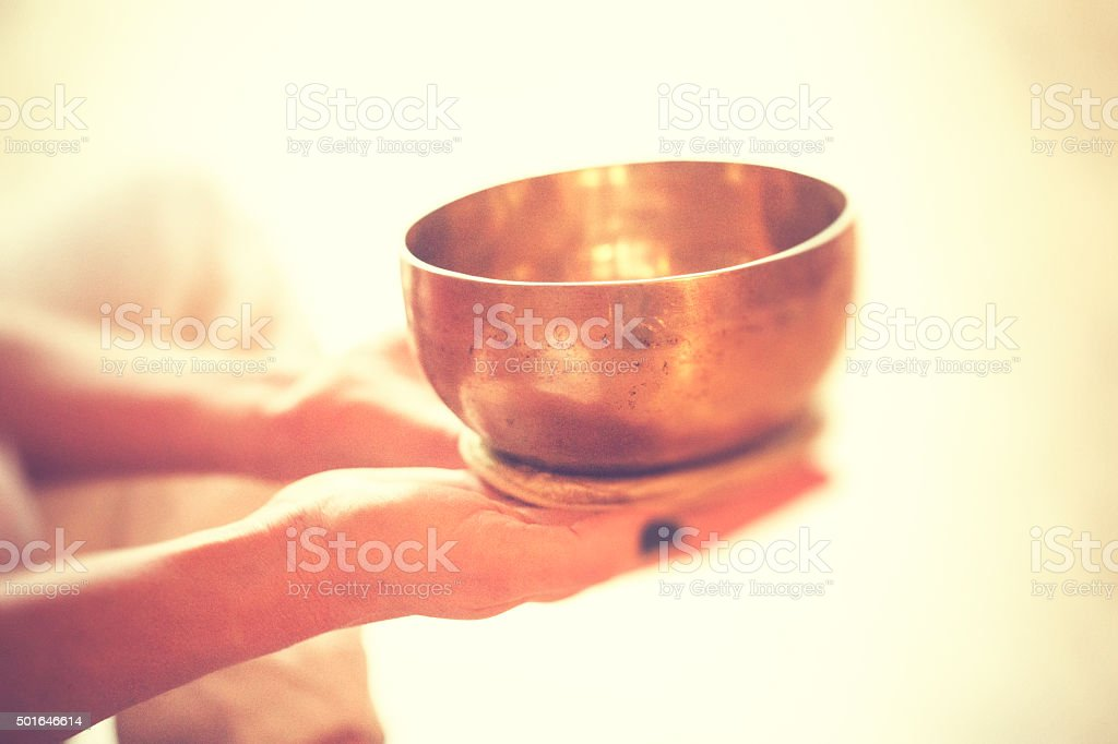 Singing bowl in hands stock photo