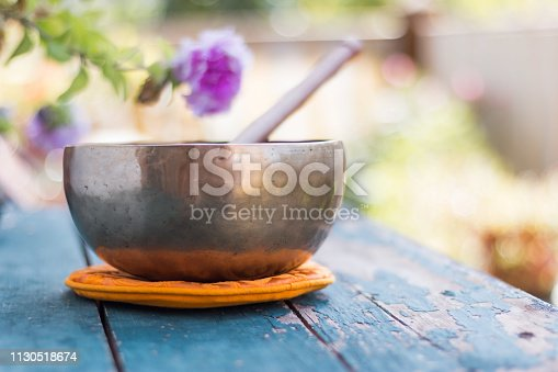 Metal singing bowl on a rustic green, wooden table outdoors. Flowers in the colourful, blurry background