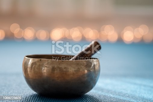 Tibetan musical instrument on yoga mat with lights in background