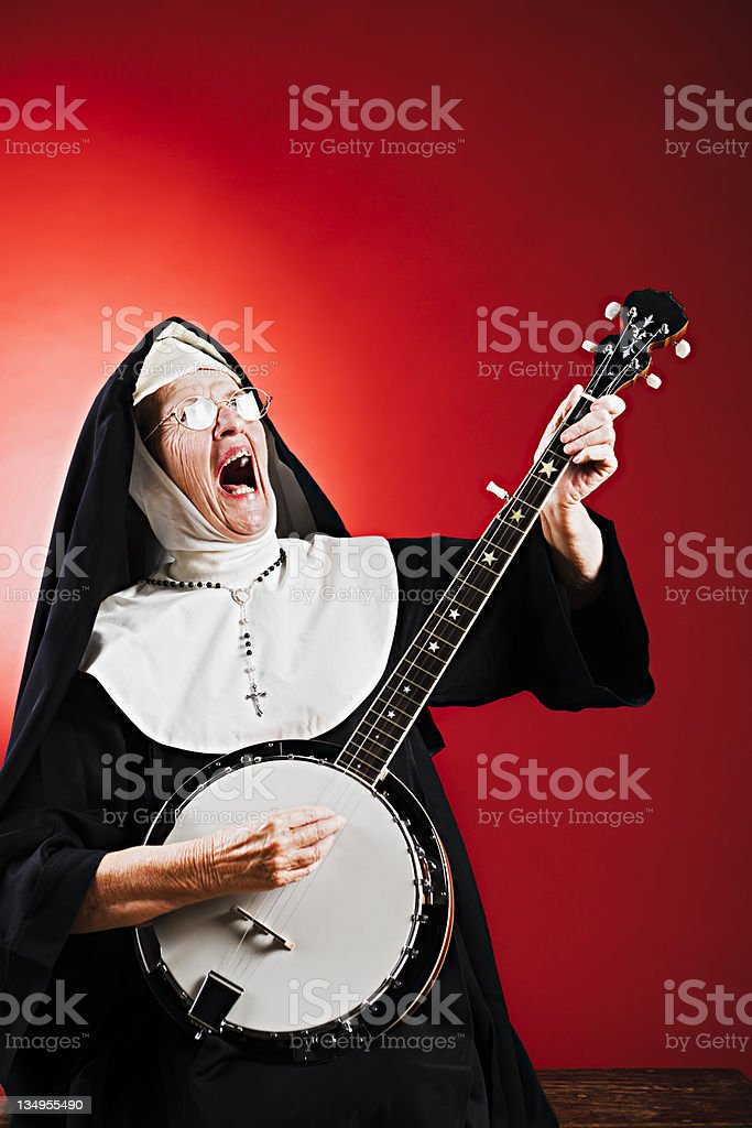 Singing ecstatically, a nun accompanies herself on the banjo. stock photo