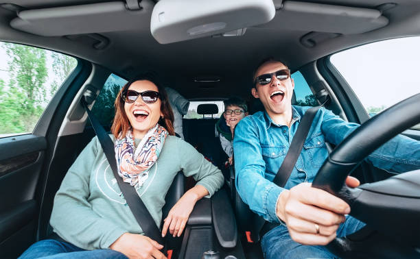 Singing family in car Cheerful young traditional family has a long auto journey and singing aloud the favorite song together. Safety riding car concept wide angle inside car view image. singing stock pictures, royalty-free photos & images