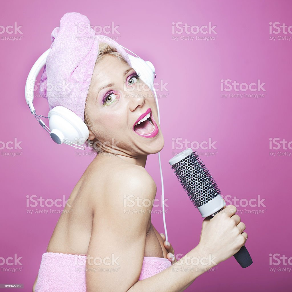 One young woman singing in the bathroom with headphones on. She is...