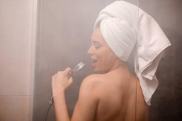 Cantando no chuveiro. Natural beleza retrato mulher jovem e bonita com uma toalha enrolada ao redor de seu cabelo, depois de tomar banho. Na casa de banho. - foto de acervo