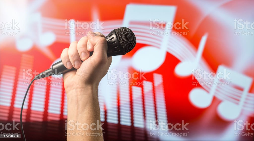 Singing, karaoke or vocal training concept. Microphone in hand in front of an abstract music themed note and equalizer background. Song contest and live performance. stock photo