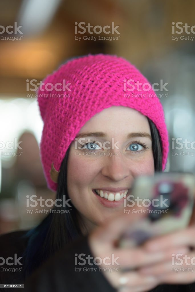 Single adult woman smiling while shopping on her smart phone stock photo