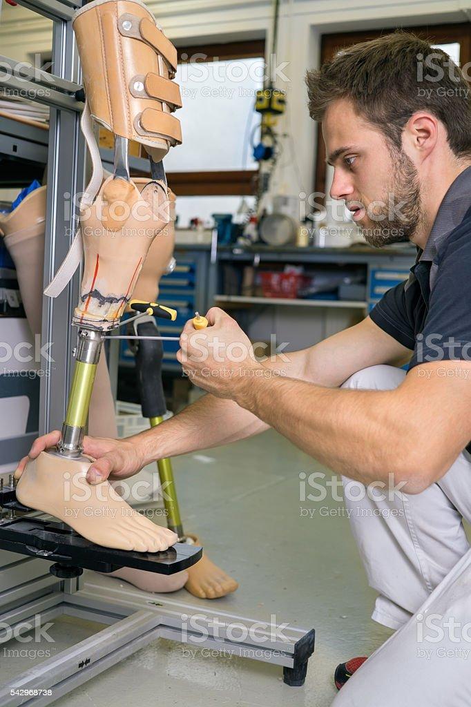 Single adult working on prosthetic leg adjustment. – Foto