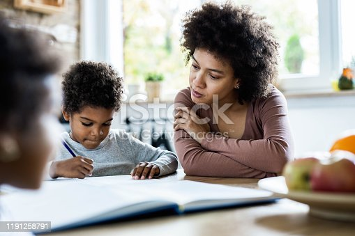 858130938 istock photo Single African American mother assisting her son with homework. 1191258791