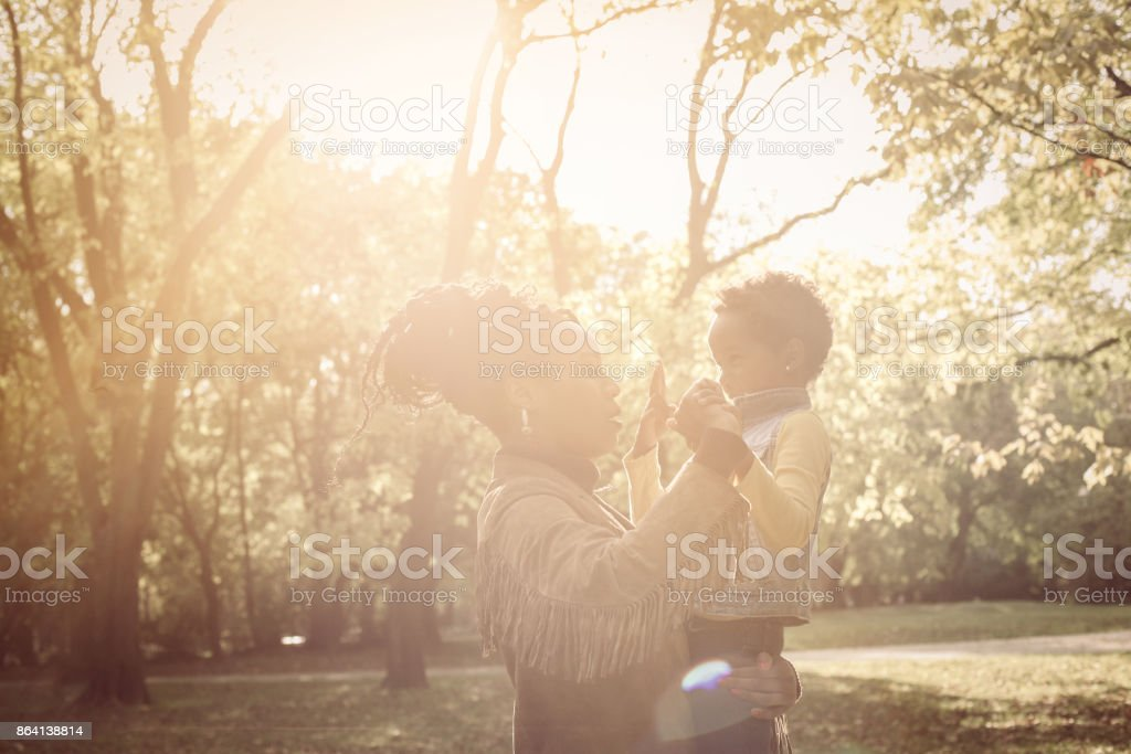Single African American mother with daughter playing in park. royalty-free stock photo