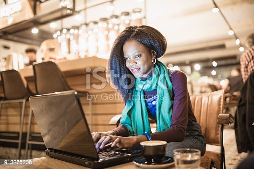 istock Single. African-American young woman enjoy coffee break and using laptop in coffee shop 913275208