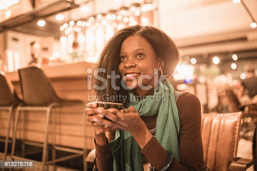 istock Single. African-American young woman enjoy coffee break and using smart phone in coffee shop 913275216
