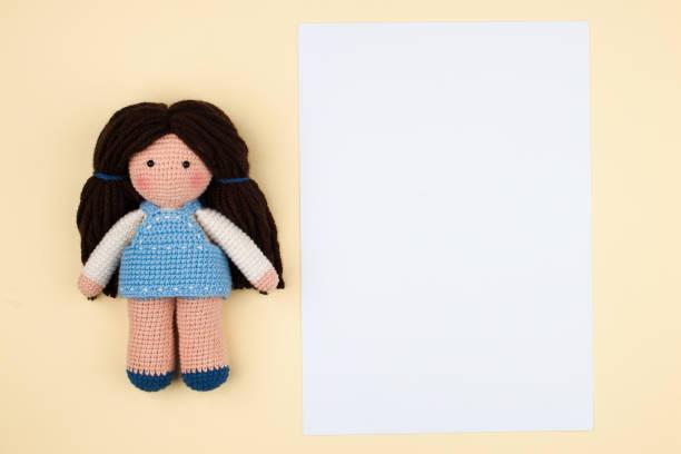 einzelne amigurumi puppe mit braunen haaren und zuschnitt für text auf gelbem hintergrund weich - kleinkinder kleid häkeln stock-fotos und bilder