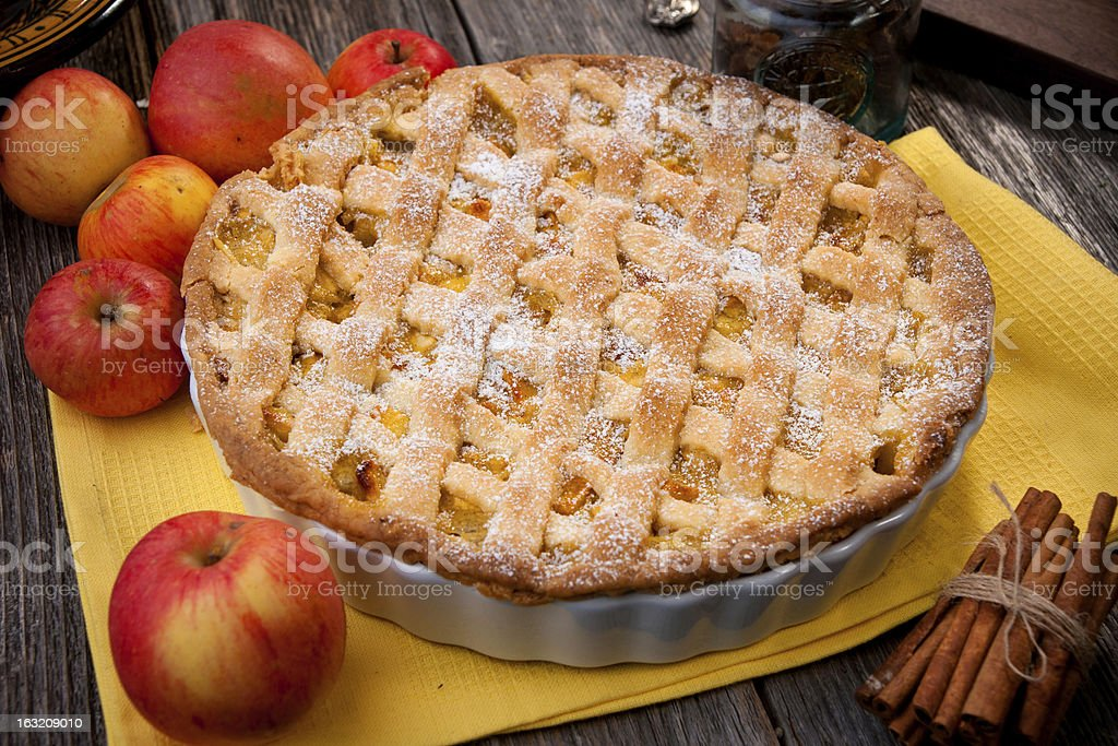 Single apple pie next to apples and cinnamon sticks stock photo