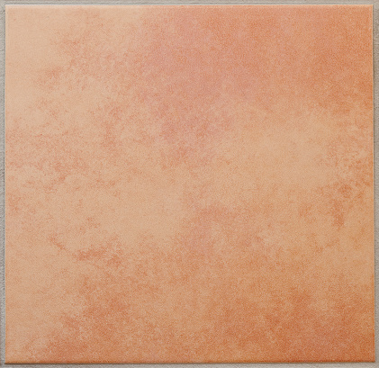 Cloudy, mottled patterned square floor tile, terracotta, surrounded by a grey tile joint or grouting. Red and sandy colored. Italian style. Square orientation. The image has been shot full frame and close up. Ideal for backgrounds. The size of the photo is 2000 x 1943 px.