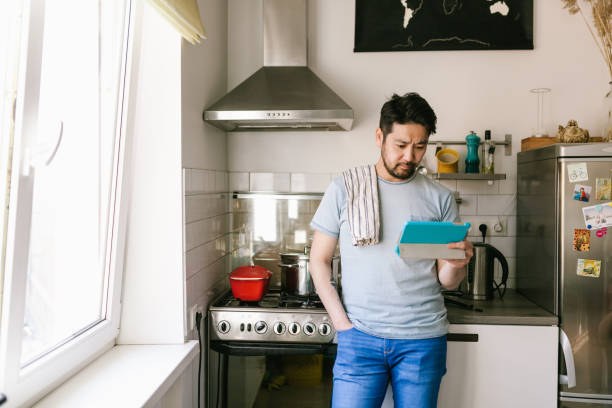 Single asian man learning to cook with digital cookbook stock photo