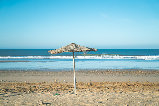 Hotel beach in tropical climate. Single straw umbrella