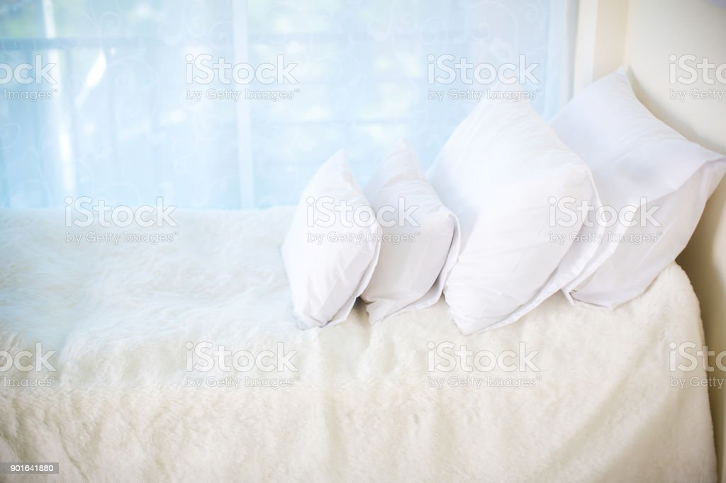Single bed with white bed sheets and many white pillows. relaxing...