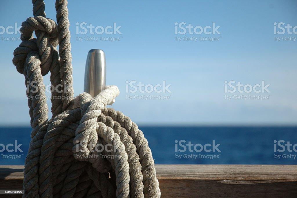 Single belay pin on sailing ship rail with ocean horizon royalty-free stock photo